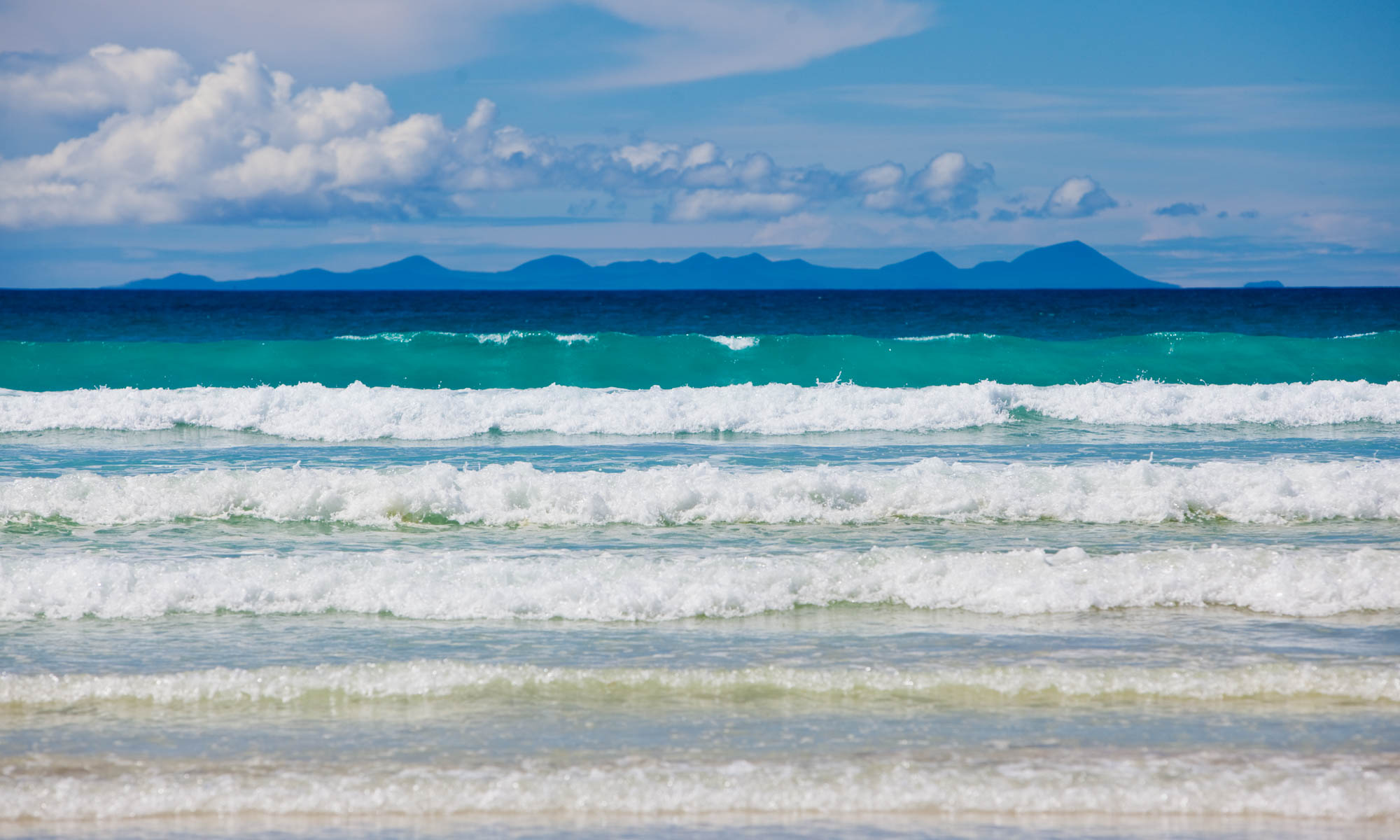 Beautiful waves in various shades of blue rolling into a beach in the Galapagos Islands with Floreana Island in the distance.