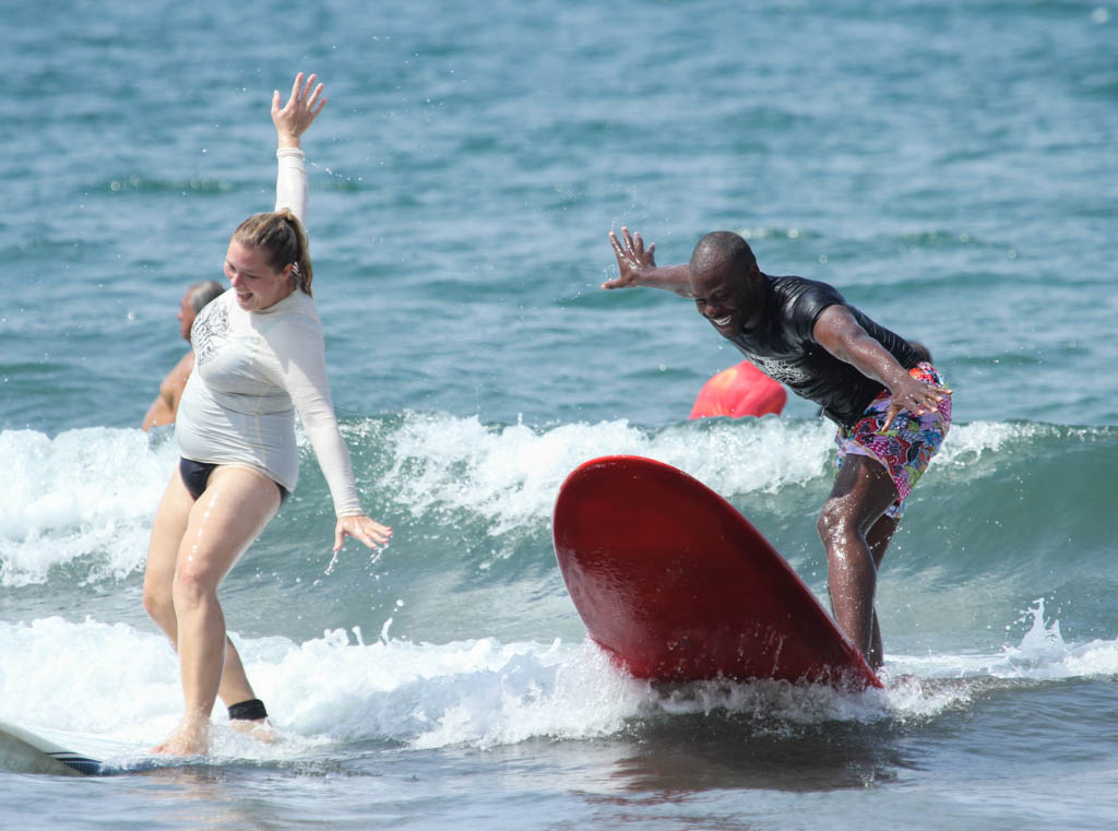 White woman and black man having fun learning to surf