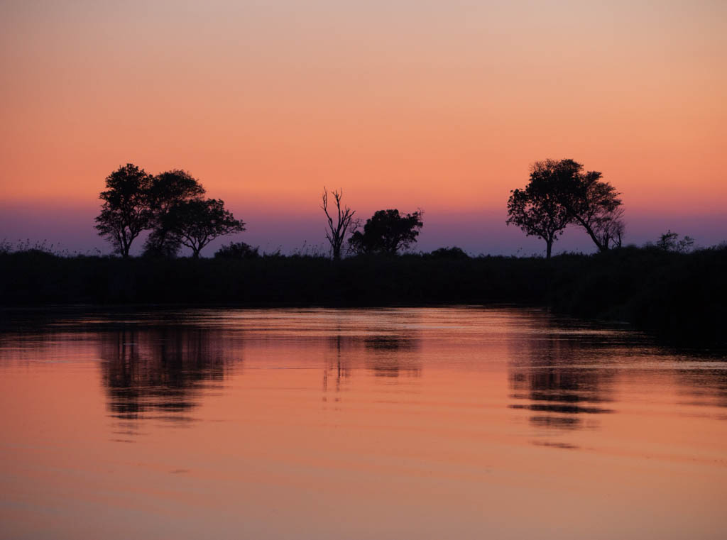 Sunset with blue, orange and purple reflecting on the waters of the Okavango Delta