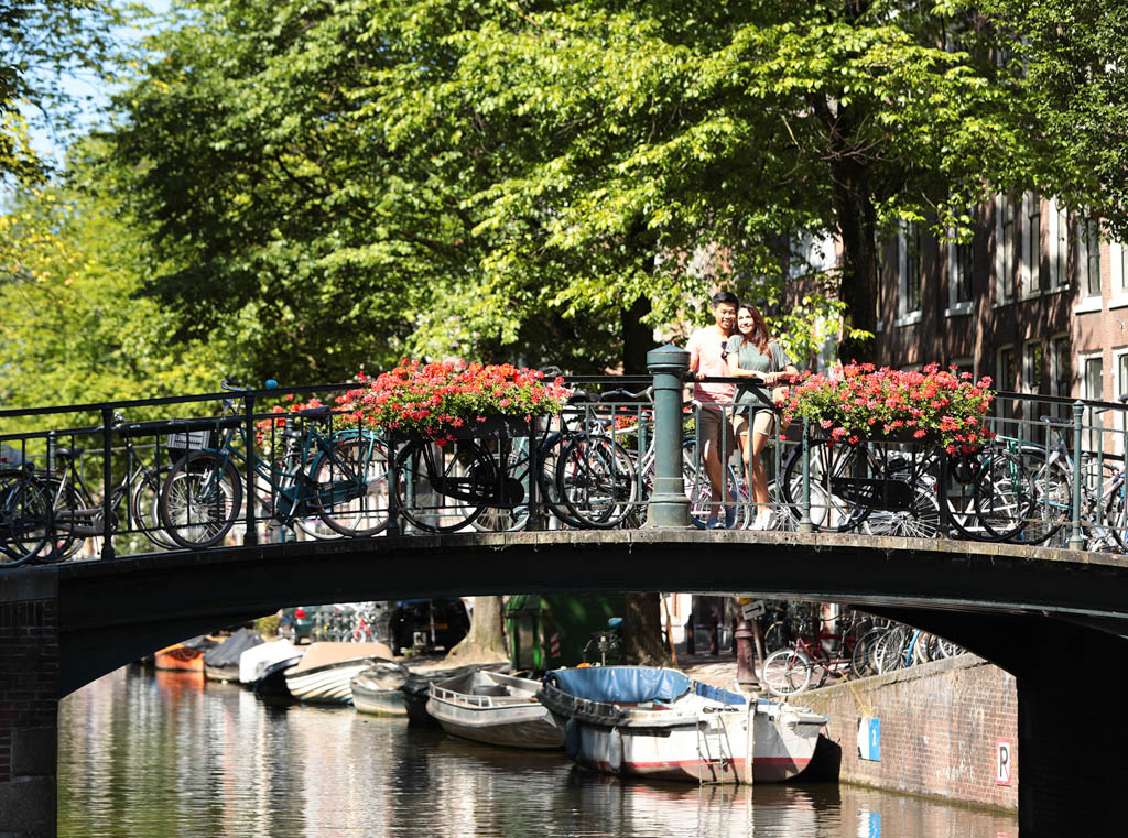Couple pose for picture on bridge in Amsterdam