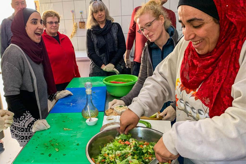 Women gather around a table preparing food