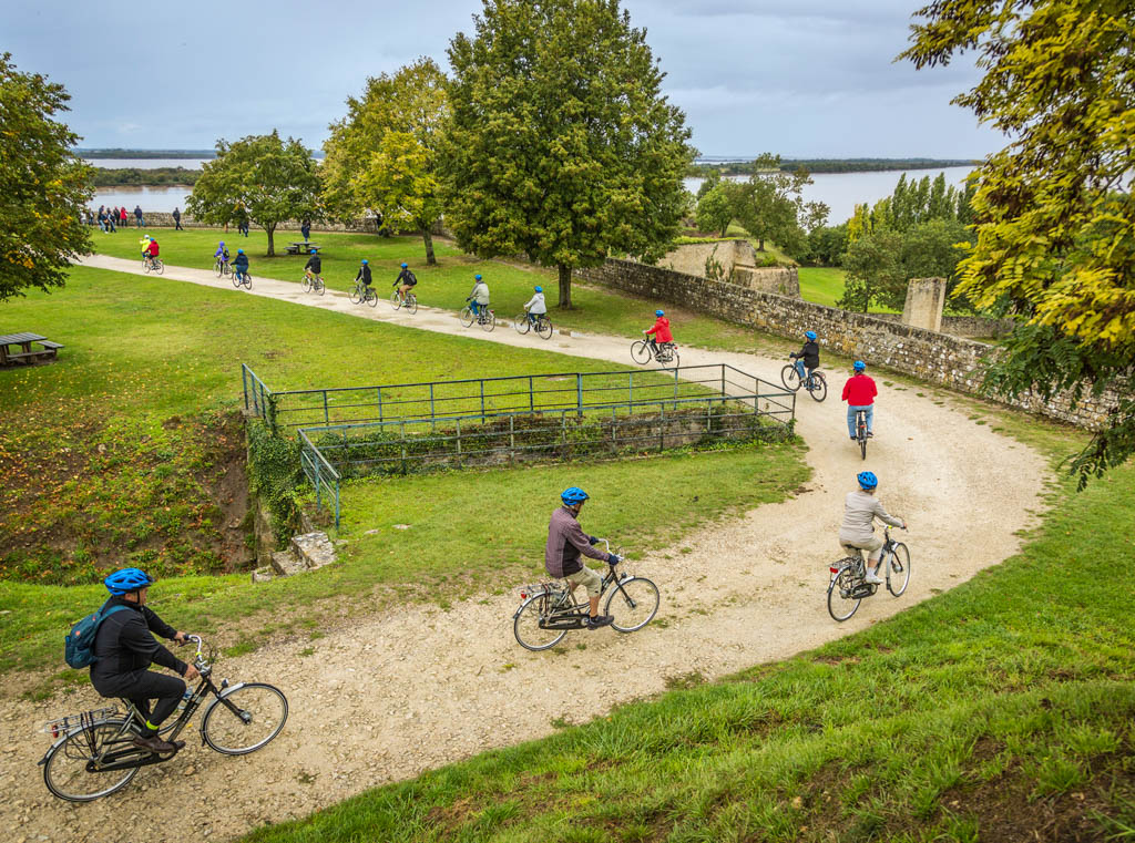 Group of travellers on cycling tour travel down dirt road in France