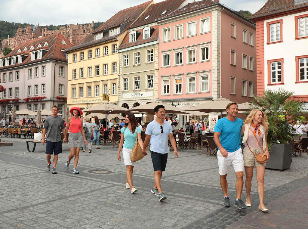 Three separate couples hold hands while walking through the streets of Heidelberg, Germany