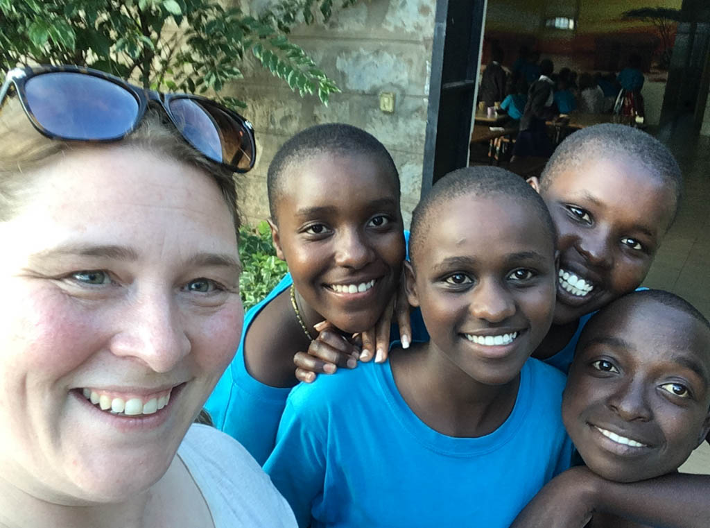 Shari Tucker and group of four Kenyan children with big smiles