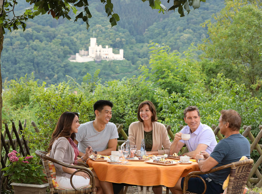 Group of smiling people enjoy a meal in front of castle in Lahnstein, Germany