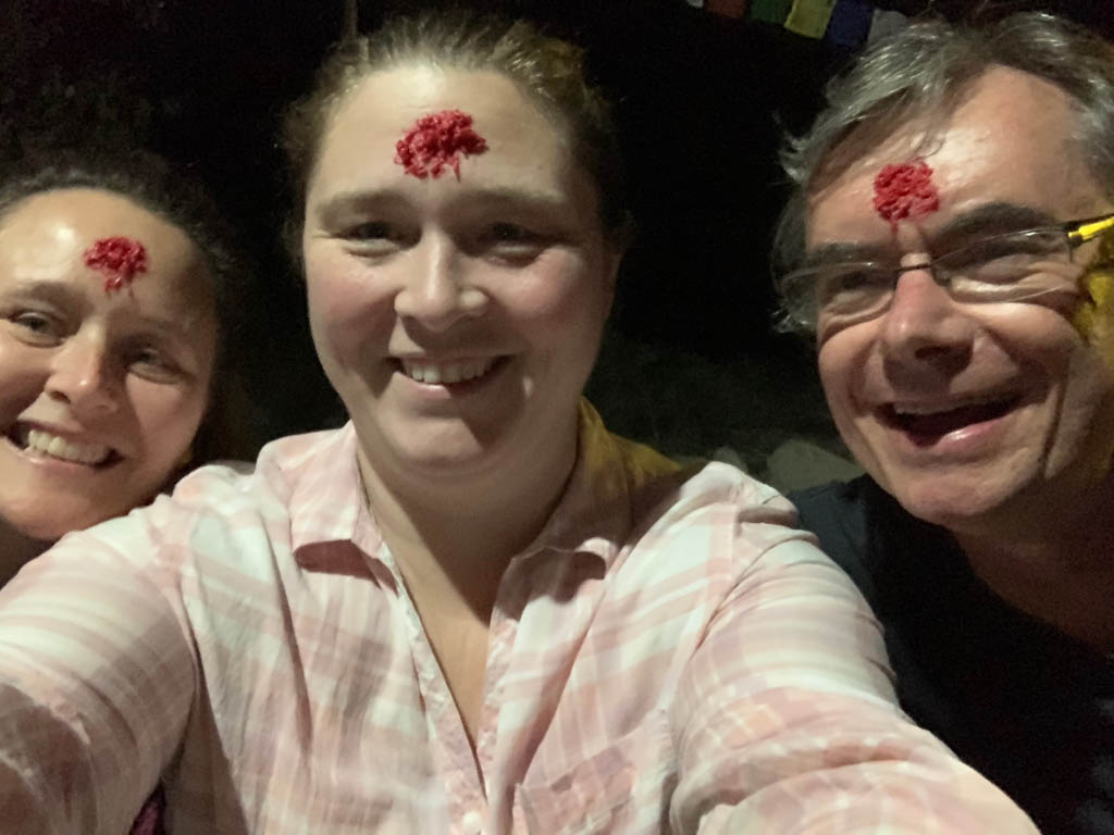 Group of three people in Nepal with red blessing on their foreheads