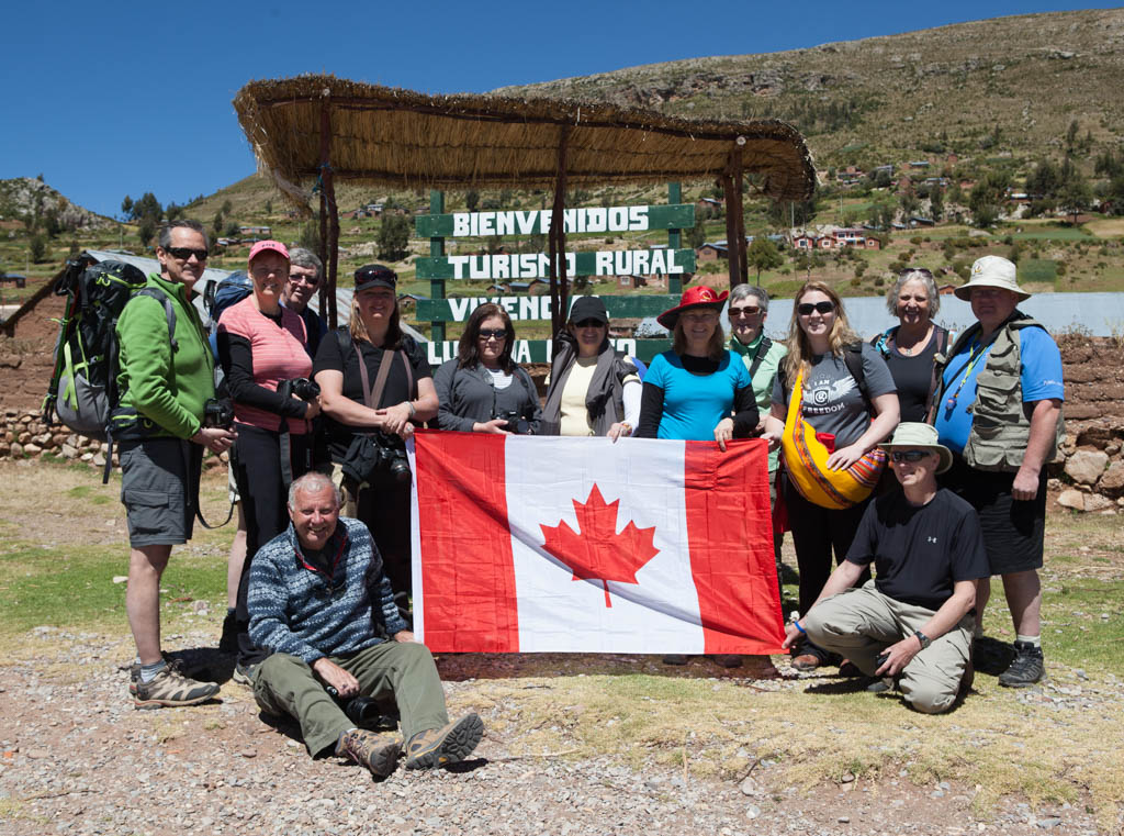 Group of travellers hold up Canadian flag in Peru