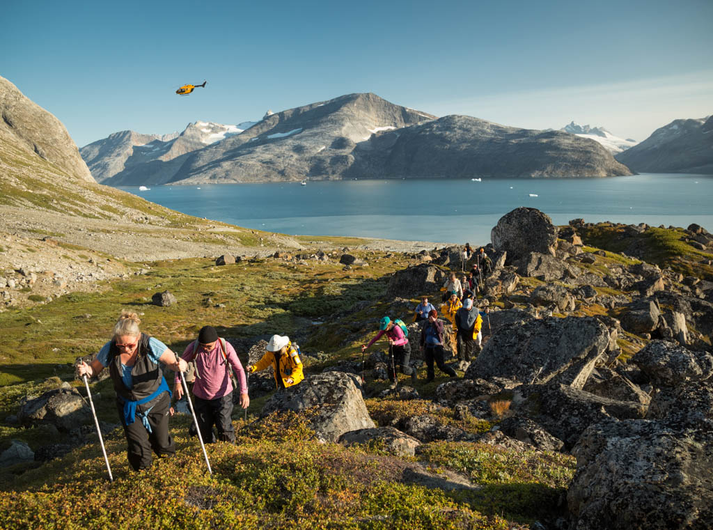 Travellers hiking through rocky terrain in Greenland with helicopter in distance
