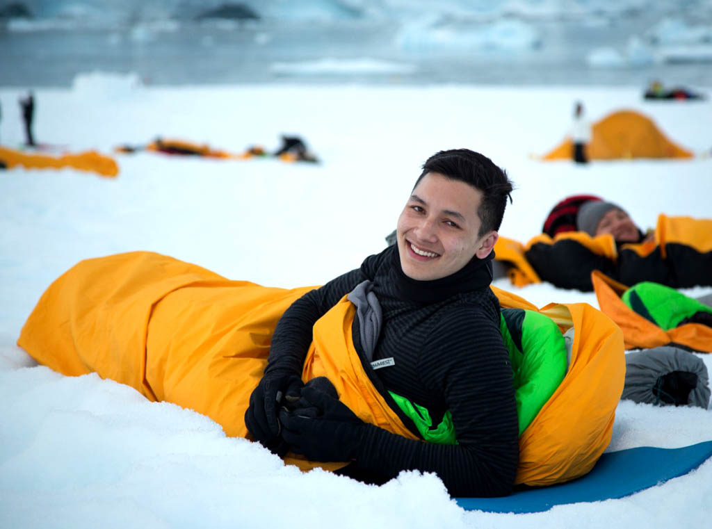 Smiling man in thermal sleeping bag surrounded by snow in Antarctica
