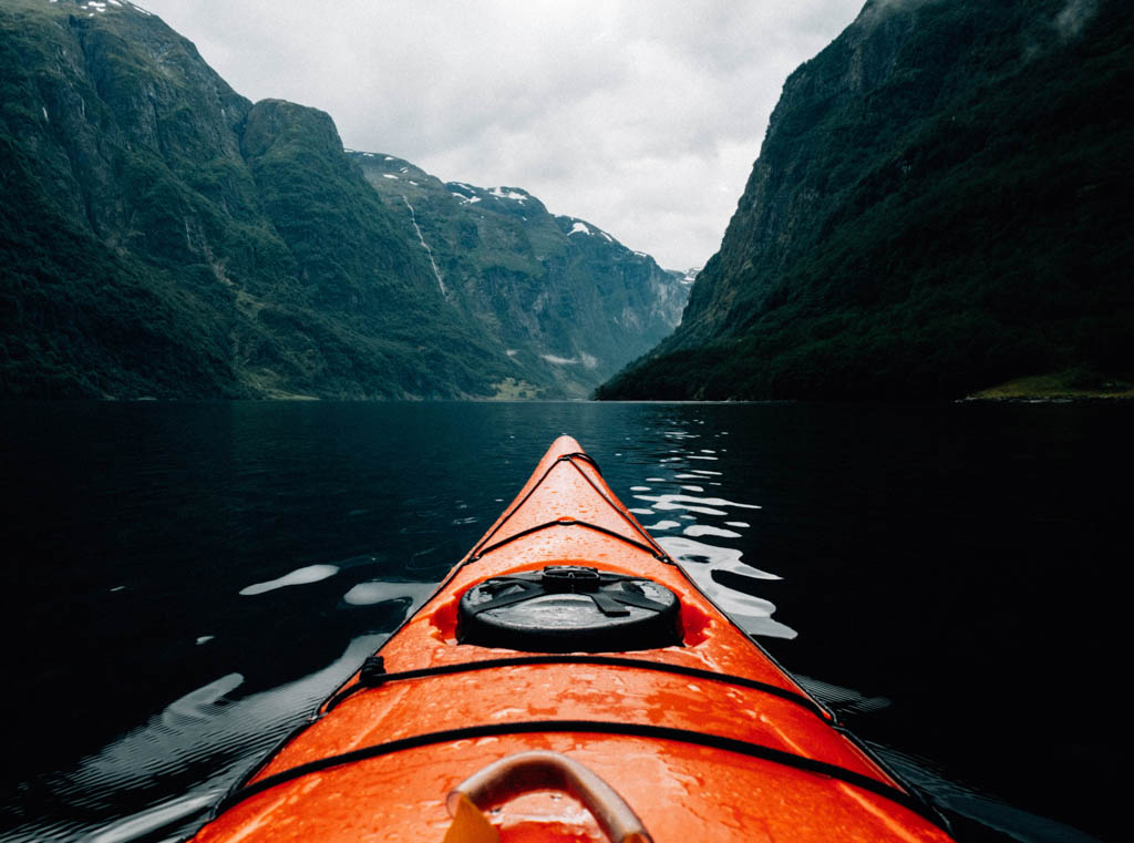 The front of an orange kayak going up river surrounded by mountains