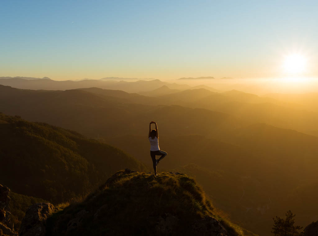 Woman doing yoga on steep hill at sunrise in Spain