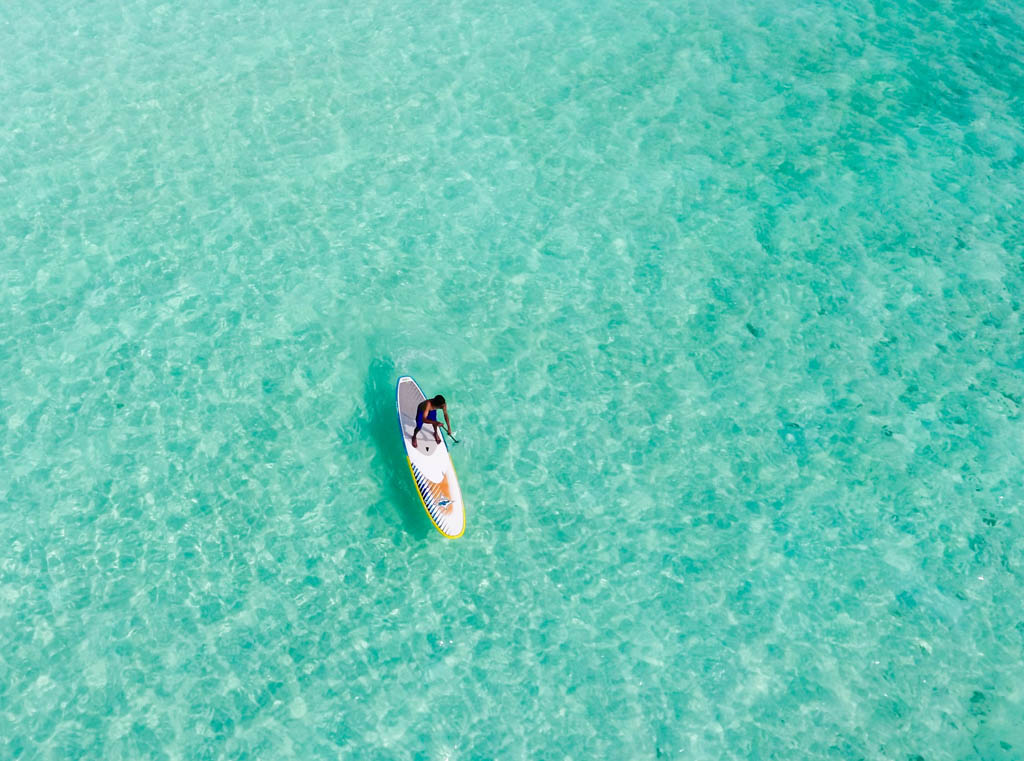 Top view of lone person paddle boarding in crystal clear waters