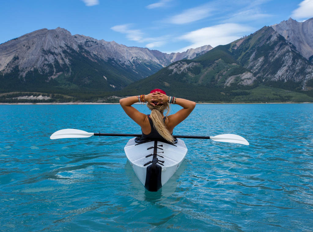 Woman relaxing in kayak with paddle resting across legs, looking at mountains in front of her