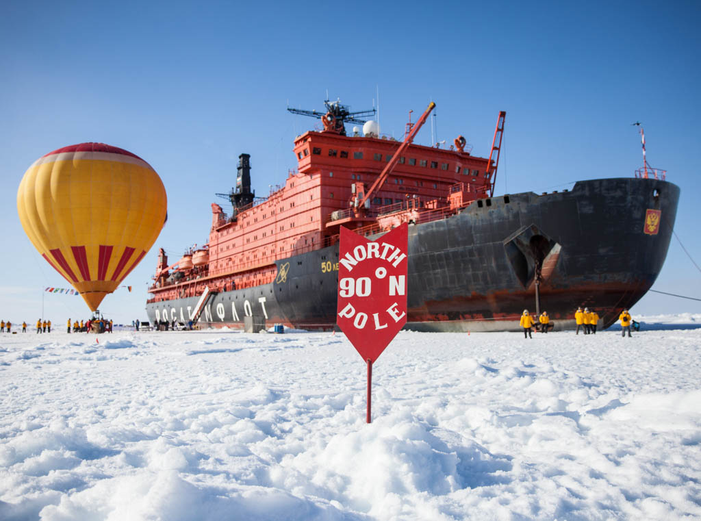 Ocean cruise ship at North Pole with hot air balloon beside it