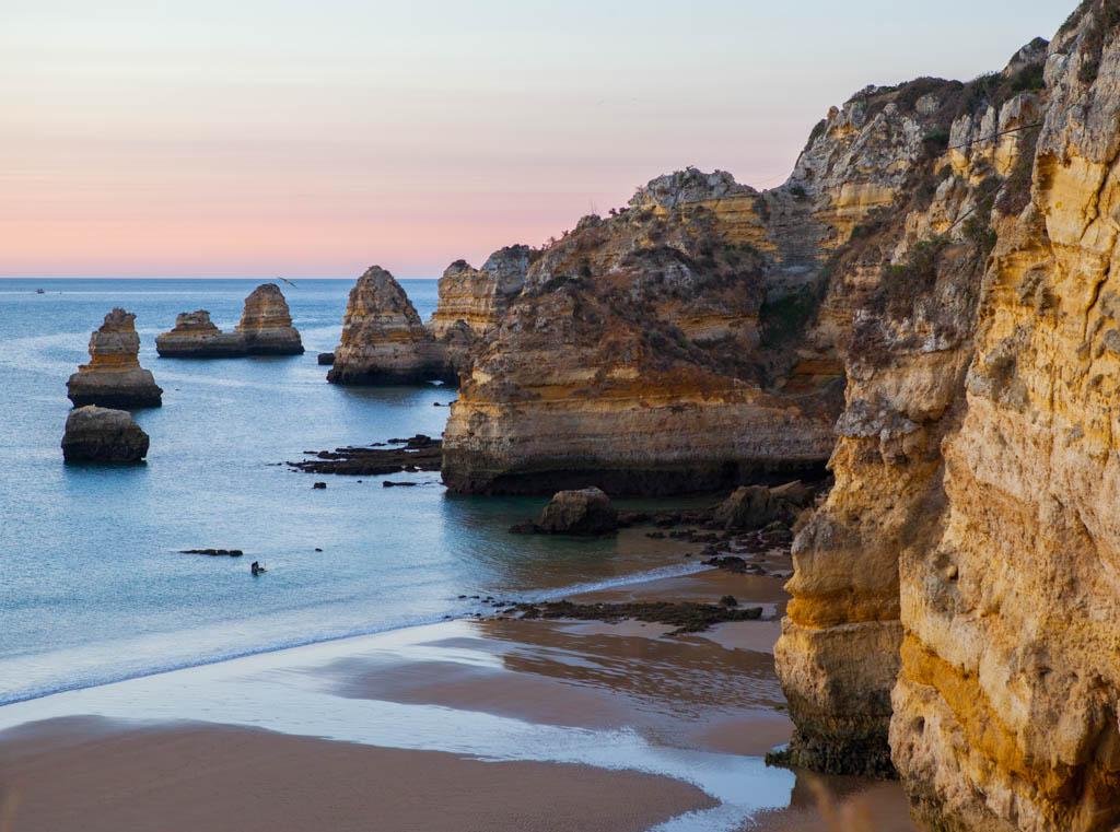 Rocky cliffs beside shoreline at sunrise in Portugal