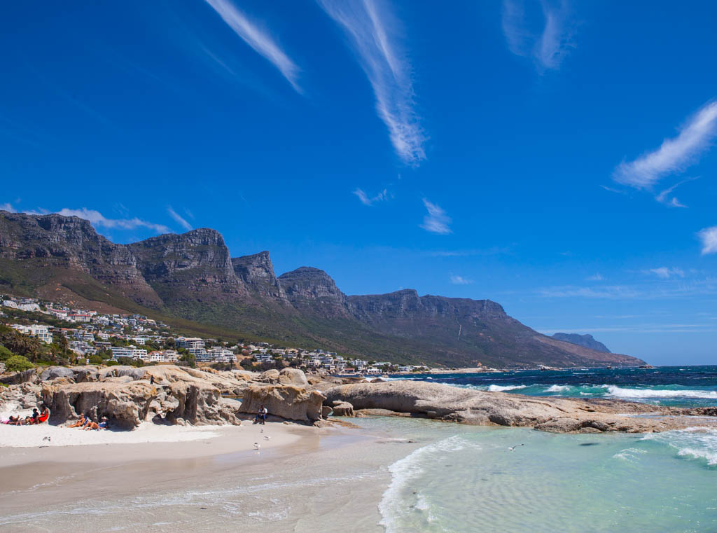 Side view of white sand beach with Twelve Apostles Mountain Range in background and blue sky