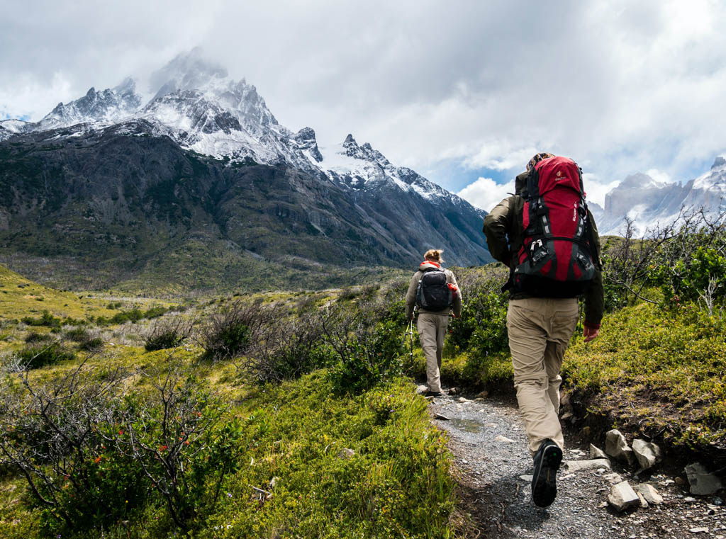 Two hikers trek over mountainous terrain