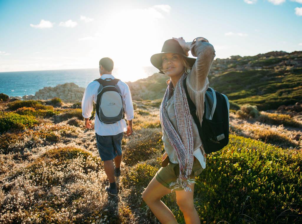 Couple hiking near ocean on a sunny day