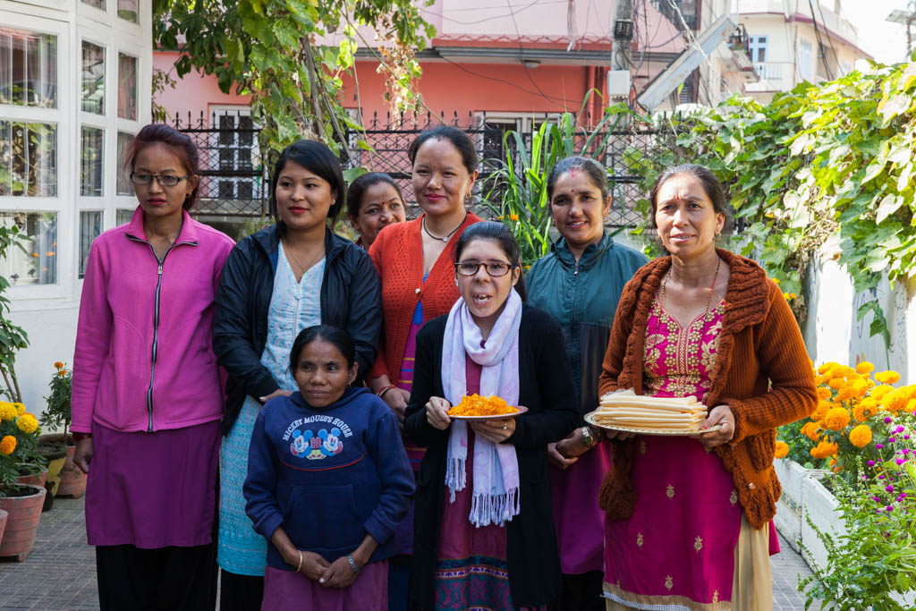 Eight Nepalese women pose for picture in an outdoor courtyard