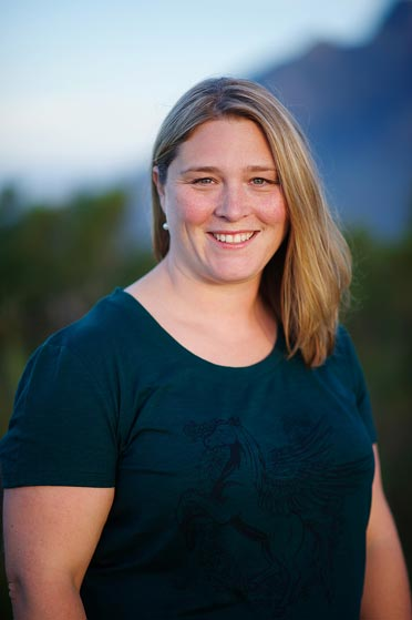 Shari Tucker smiling at the camera. She is wearing a dark teal shirt against a mountain scene