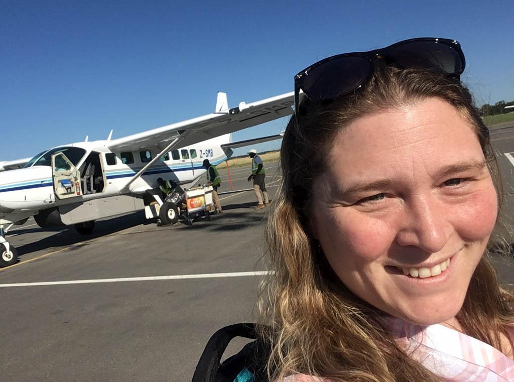 Shari Tucker in front of small bush plane in Zimbabwe