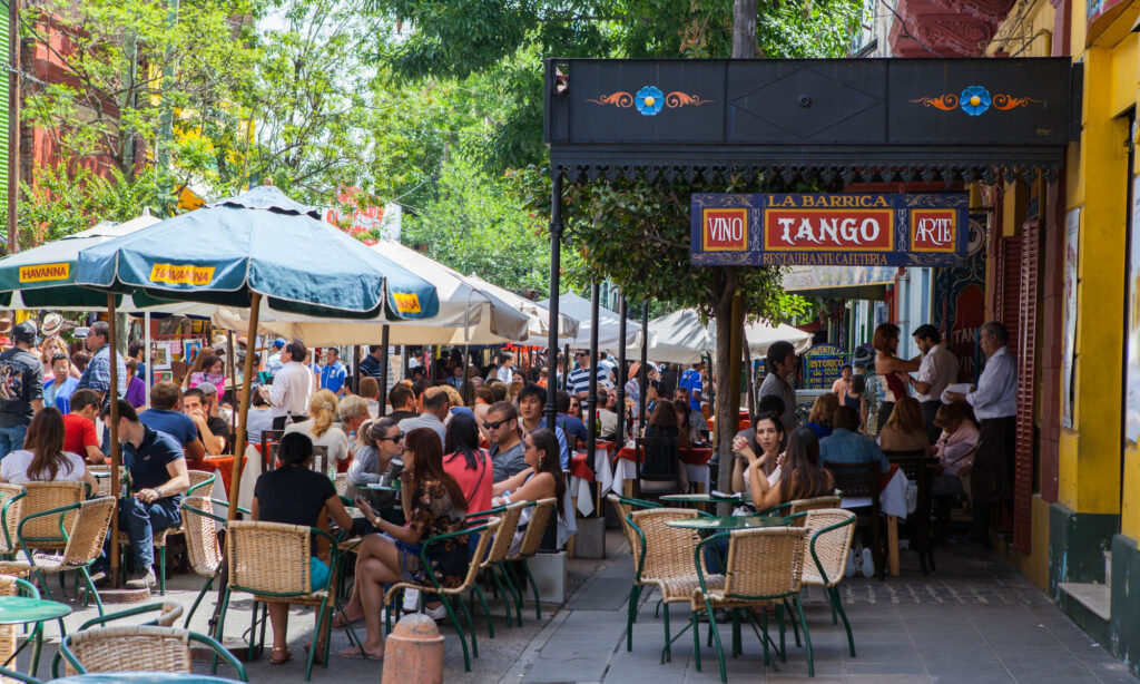 Busy street full of people and cafes in Buenos Aires with a Tango sign by the restaurant