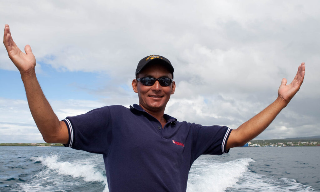 Man on boat with arms outstretched and smile on his face