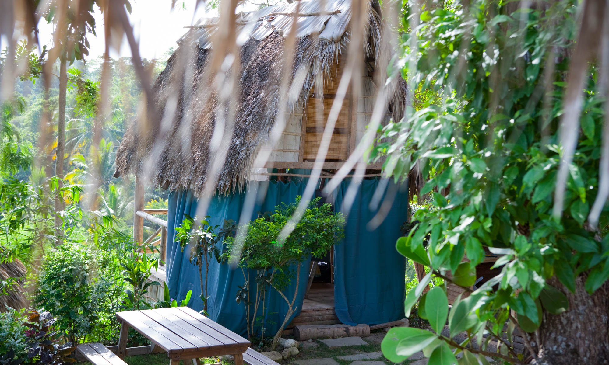 Rustic accommodation with a thatched roof and blue fabric for privacy with green foliage and a picnic table