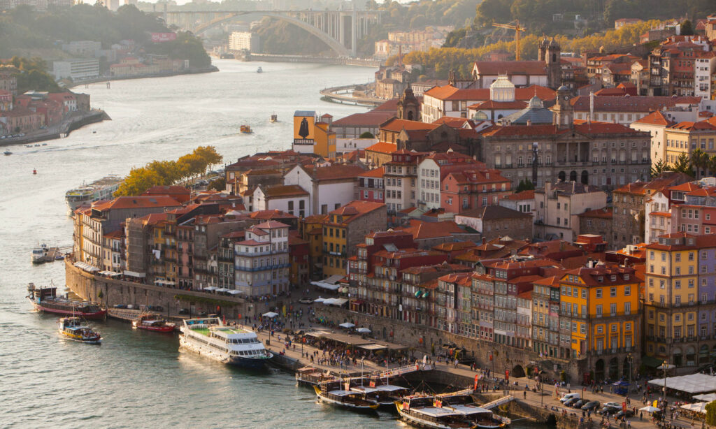 View of the Douro River and historic district of Porto, Portugal with boats along the river