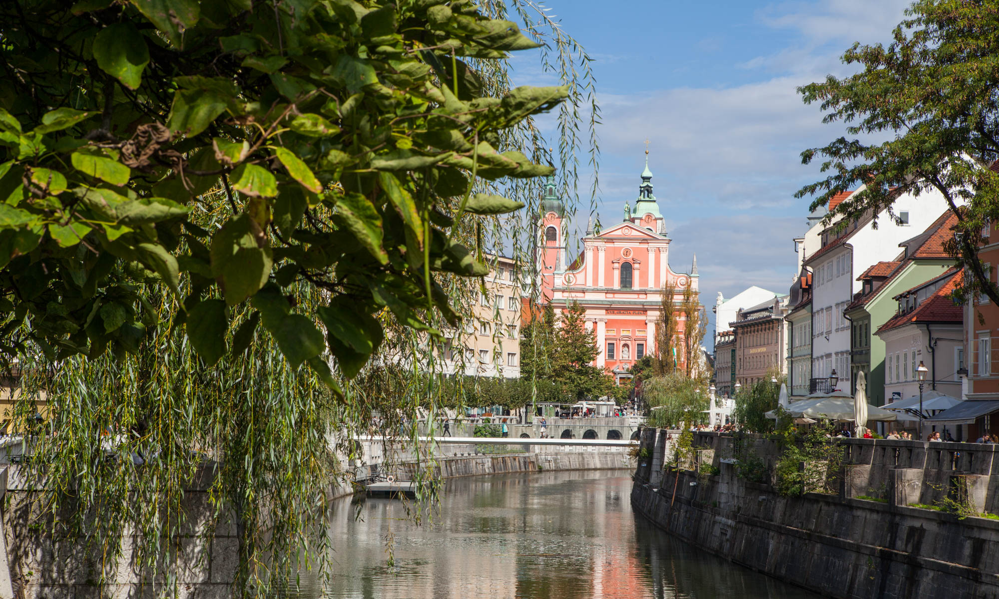 View of a pink building along the river in Ljubljana, Slovenia with green foliage