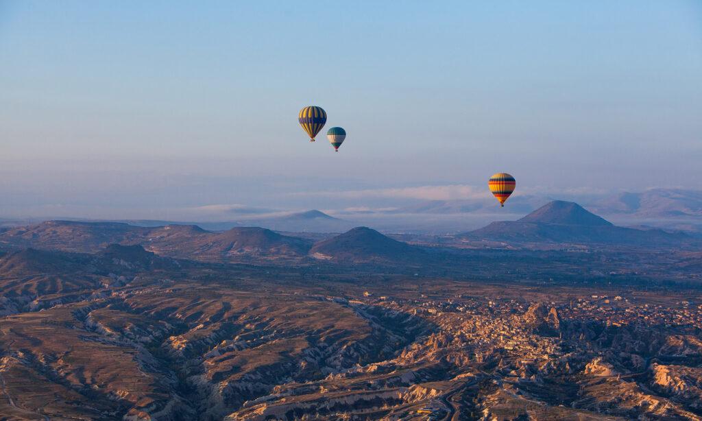 Three hot air balloons raising above the rough landscape of Cappadocia, Turkey at sunrise
