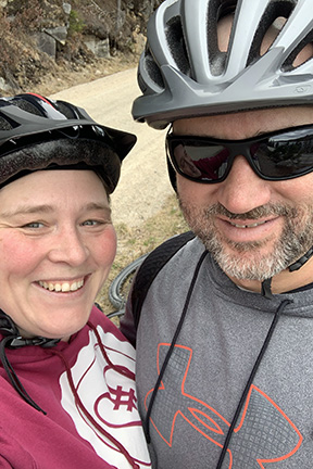 two people in sweatshirts and bike helmets smiling at the camera