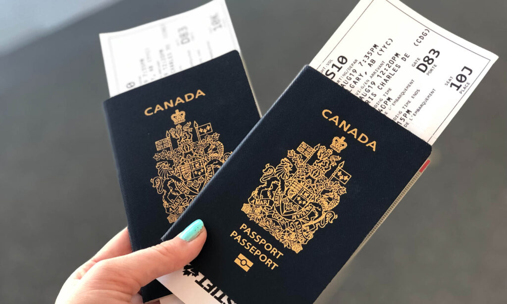Close up of two Canadian passports being held by a person with blue nail polish
