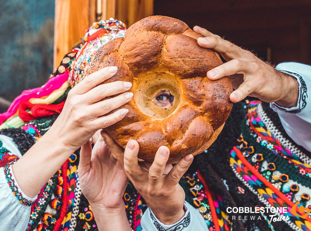 Two Ukrainian people peaking through the centre of a loaf of traditional bread