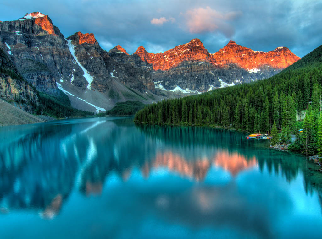 mountains in Alberta Canada with sun kissed peaks and a lake and forest in the foreground
