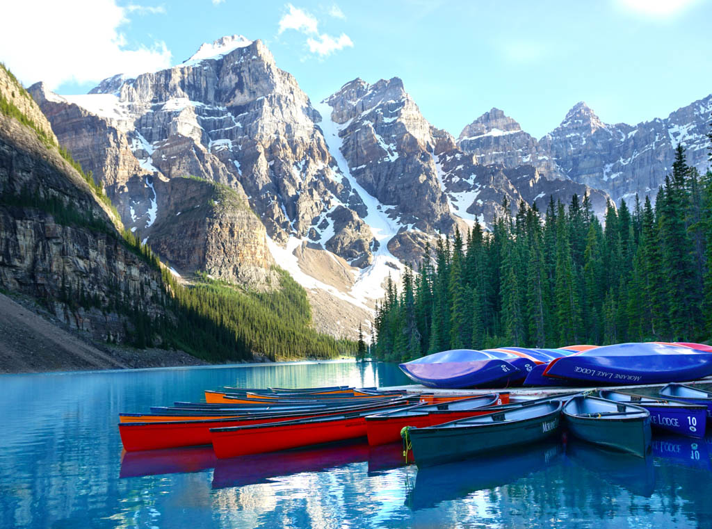 Lake with multi coloured canoes with snow capped mountains in Alberta Canada in the background