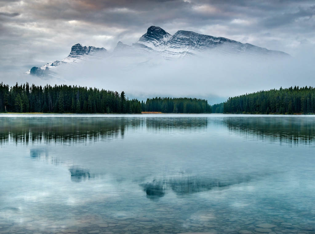 Lake Minnewanka Alberta with mountains in the background shrouded in fog