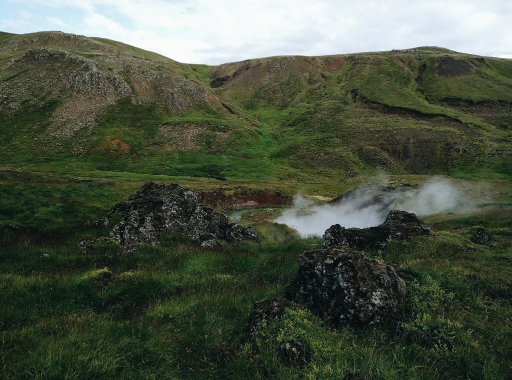Steaming hot springs surrounded by rocks and green hills in Reykjadalur Iceland