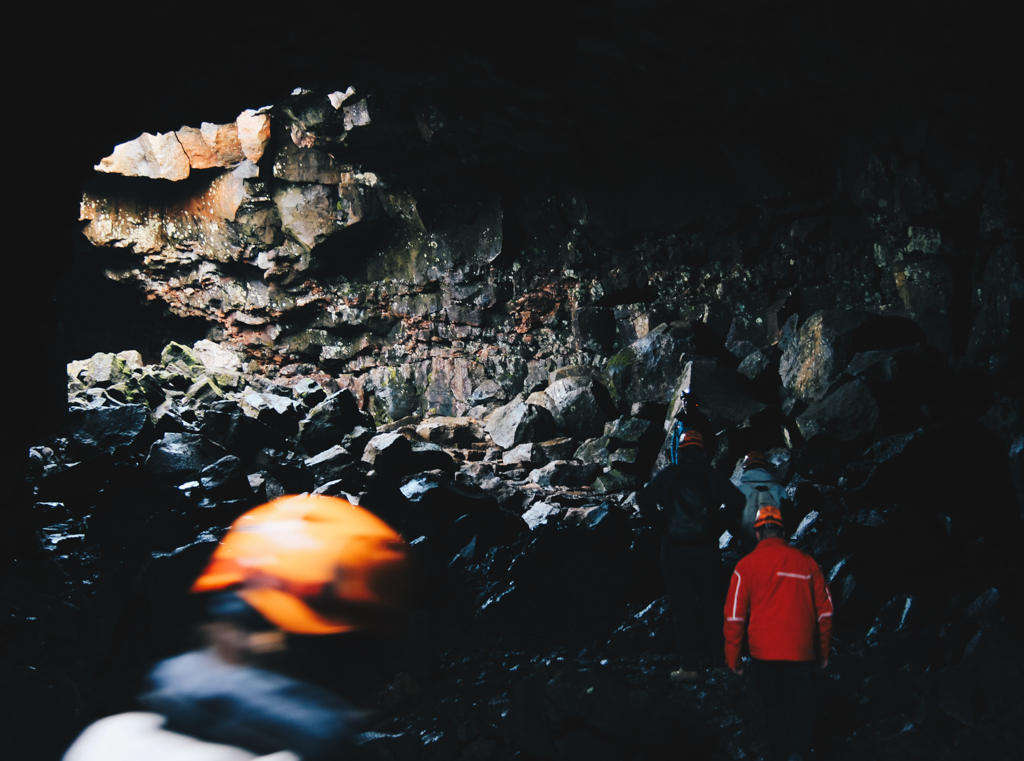 Two people with safety gear walking through a lava tunnel in Iceland