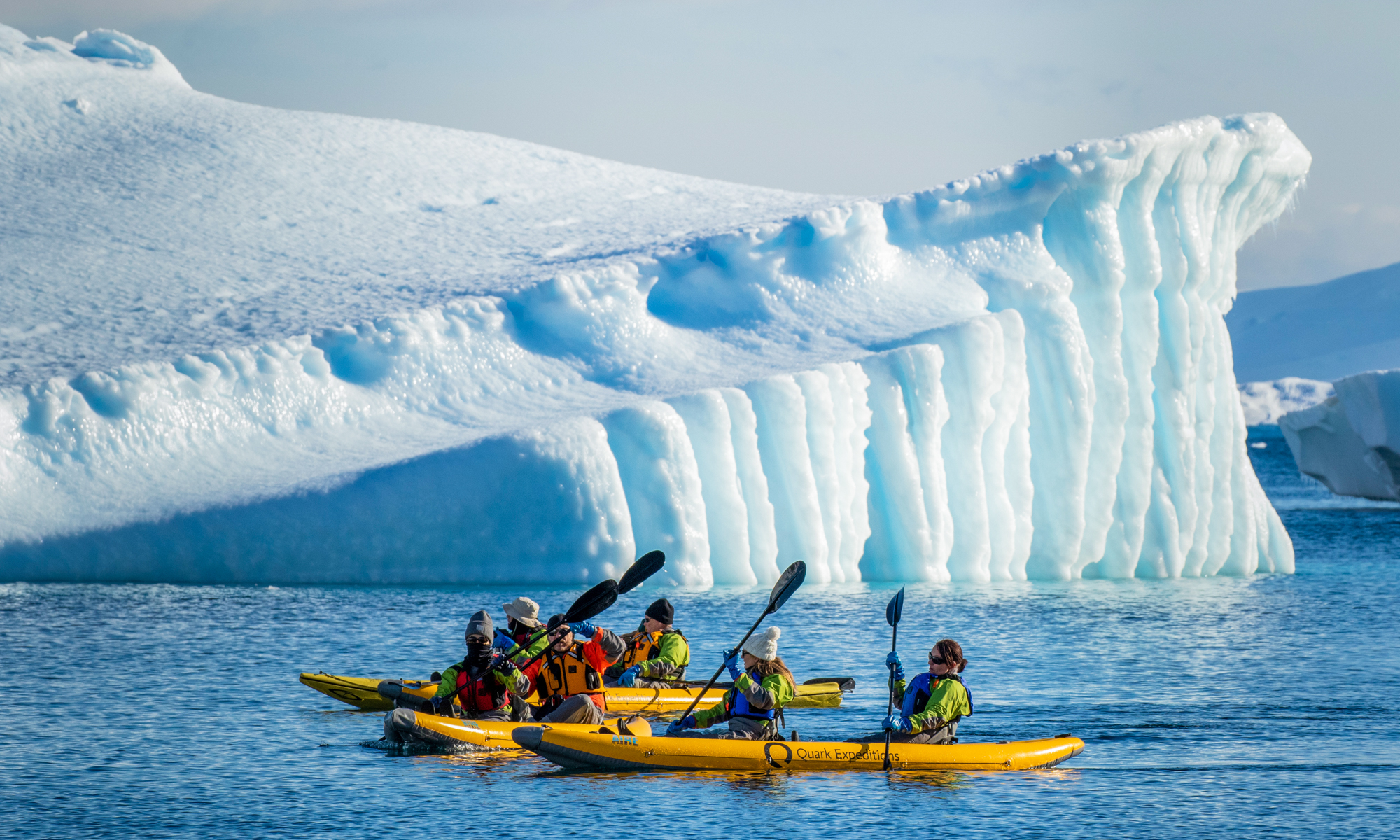 group of people paddling in yellow inflatable kayaks near a blue and white iceberg in Antarctica