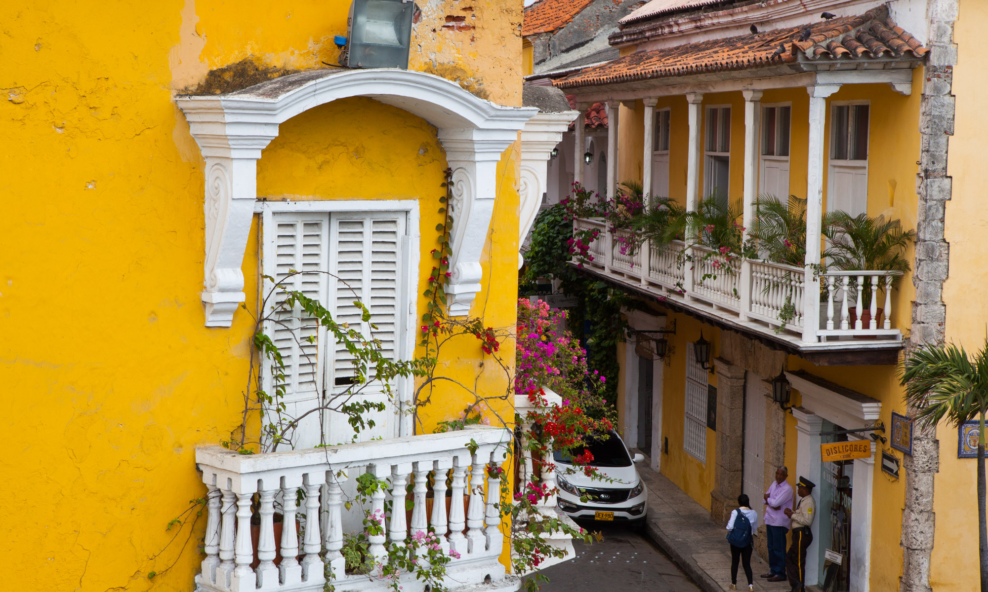 street corner with historical yellow buildings and white terraces with red and pink flowers in the historic centre of Cartagena Colombia